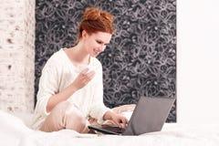 Muchacha pelirroja en la cama que trabaja en el ordenador portátil y el café de consumición fotos de archivo libres de regalías