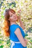 Muchacha pelirroja en una cereza floreciente cercana del vestido azul imagenes de archivo