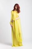Muchacha pelirroja en vestido amarillo elegante largo imagen de archivo