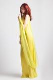 Muchacha pelirroja en vestido amarillo elegante largo Imagenes de archivo