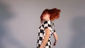 Muchacha pelirroja feliz hermosa en el baile y el salto del vestido del modelo en estudio metrajes