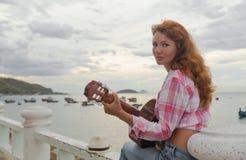 Muchacha pelirroja hermosa con una guitarra Foto de archivo