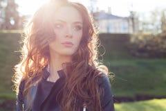 Muchacha pelirroja hermosa en el sol en una chaqueta negra en el parque de la ciudad Imagen de archivo