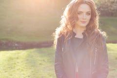 Muchacha pelirroja hermosa en el sol en una chaqueta negra en el parque de la ciudad Fotos de archivo libres de regalías