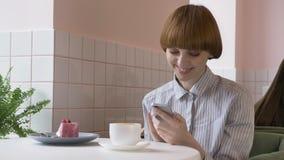 Muchacha pelirroja hermosa joven que se sienta en un café, usando un smartphone, el mandar un SMS, sonriendo 60 fps almacen de video