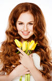 Muchacha pelirroja hermosa, sosteniendo tulipanes amarillos en una parte posterior del blanco imagen de archivo