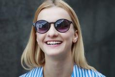 Muchacha pelirroja joven en gafas de sol con los vidrios oscuros en un marco, día, al aire libre Foto de archivo