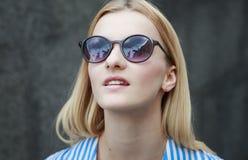 Muchacha pelirroja joven en gafas de sol con los vidrios oscuros en un marco, día, al aire libre Foto de archivo libre de regalías