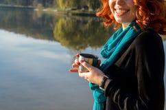 Muchacha pelirroja joven que sostiene en sus manos a la taza fotos de archivo libres de regalías