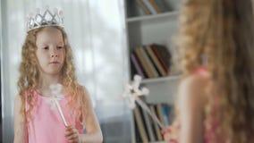 Muchacha pelirroja que desempeña papel de la hada mágica delante del espejo, actriz futura almacen de video
