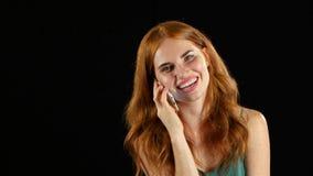 Muchacha pelirroja que habla en el teléfono Fondo negro almacen de video
