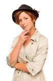 Muchacha pelirroja que lleva una trenca y un sombrero Imagen de archivo