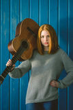 Muchacha pelirroja que se coloca con la guitarra acústica Foto de archivo
