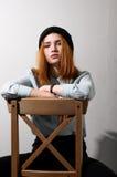 Muchacha pelirroja que se sienta en una silla Fotografía de archivo