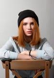Muchacha pelirroja que se sienta en una silla Fotografía de archivo libre de regalías