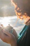 Muchacha pelirroja que sostiene en sus manos a la taza del termo cerca del lago fotografía de archivo libre de regalías