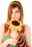 Muchacha pelirroja que sostiene la flor sonriente grande Imagen de archivo