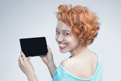 Muchacha pelirroja que sostiene un ordenador de la tableta Imagen de archivo