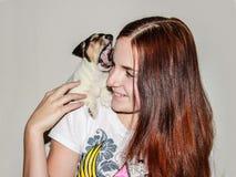 Muchacha pelirroja que sostiene un perrito Jack Russell foto de archivo libre de regalías