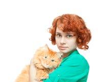 Muchacha pelirroja rizada con un gato rojo aislado Imagen de archivo