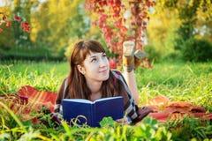Muchacha pelirroja soñadora hermosa con un libro Fotografía de archivo libre de regalías