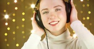 Muchacha pelirroja sonriente que disfruta de escuchar la música