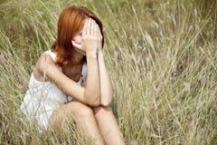 Muchacha pelirroja triste en la hierba. Foto de archivo libre de regalías