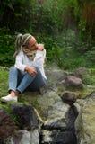 Muchacha pensativa bastante joven que se sienta por algunas rocas Foto de archivo
