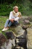 Muchacha pensativa bastante joven que se sienta por algunas rocas Imágenes de archivo libres de regalías