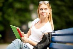 Muchacha pensativa con la tableta en su sentarse de las manos Imagen de archivo