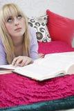 Muchacha pensativa con los libros en cama Fotos de archivo