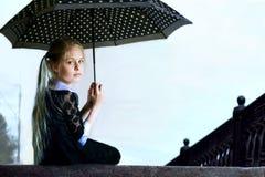 Muchacha pensativa con un paraguas En estilo retro Imagenes de archivo