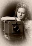 Muchacha pensativa con una cámara vieja Imagen de archivo