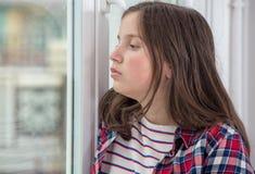 Muchacha pensativa del adolescente cerca de la ventana Foto de archivo