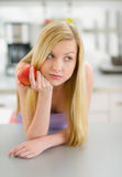 Muchacha pensativa del adolescente con la manzana en cocina Imagen de archivo libre de regalías