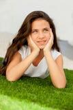 Muchacha pensativa del adolescente que miente en la hierba Imagen de archivo libre de regalías