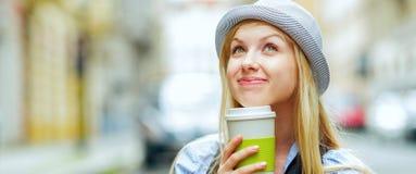 Muchacha pensativa del inconformista con la taza de bebida caliente en la calle de la ciudad Fotografía de archivo