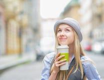 Muchacha pensativa del inconformista con la taza de bebida caliente en la calle de la ciudad Fotos de archivo