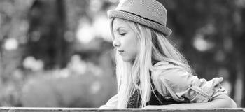 Muchacha pensativa del inconformista que se sienta en banco en el parque Fotos de archivo