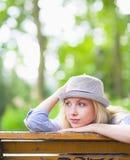 Muchacha pensativa del inconformista que se sienta en banco en el parque Foto de archivo
