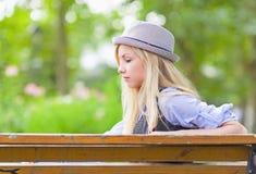 Muchacha pensativa del inconformista que se sienta en banco en el parque Fotografía de archivo