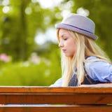 Muchacha pensativa del inconformista que se sienta en banco en parque Imagen de archivo