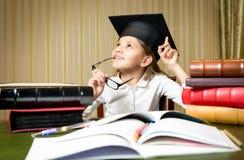 Muchacha pensativa elegante que presenta en el escritorio en casquillo de la graduación Foto de archivo libre de regalías