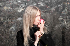 Muchacha pensativa hermosa con la rosa del rojo a disposición imagenes de archivo