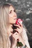 Muchacha pensativa hermosa con la rosa del rojo a disposición Imagen de archivo libre de regalías