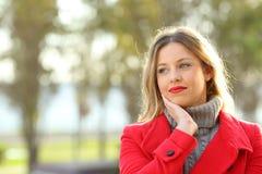 Muchacha pensativa que lleva una chaqueta roja en invierno Foto de archivo libre de regalías