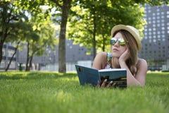 Muchacha pensativa que miente en la hierba verde con el libro Imagenes de archivo