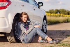 Muchacha pensativa que se inclina contra el neumático del vehículo Imagen de archivo libre de regalías