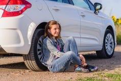 Muchacha pensativa que se inclina contra el neumático del vehículo Fotografía de archivo