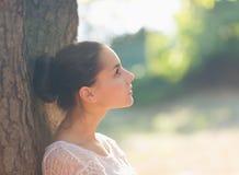 Muchacha pensativa que se inclina en árbol Fotografía de archivo libre de regalías